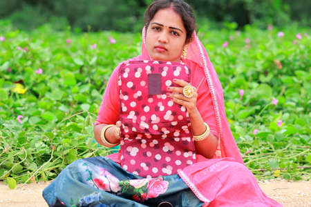 A young Indian fashion artist woman sitting in the garden, holding the Wallet bag in her hand and looking at the camera, thinking about the solution to the make-up business problems ahead of her
