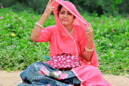 An Indian adult fashion artist woman sitting in the garden, lifting the veil with her hand and looking away with a smiling face