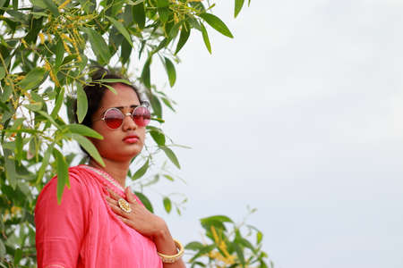 Young woman posing in a beautiful traditional dress and wearing style sunglasses. concept Summer fashion, promotion and indigenous practice of Indian culture, nature of natural beauty