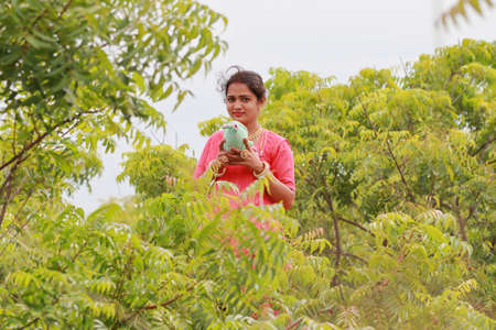 An Indian traditional woman holding a teddy bear and posing in the field 免版税图像