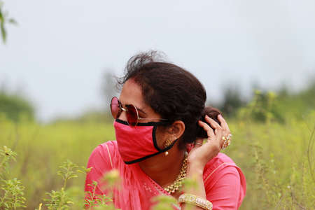 An Indian young stylish woman posing in a field wearing a red face mask to prevent corona disease,Concept to protect farmers, laborers, Outdoor workers, gardener,
