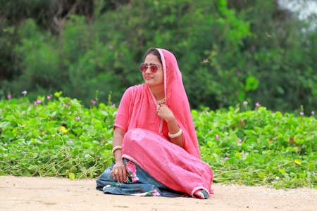 A young woman posing in the garden wearing sun glasses