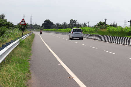 Chennai, Tamil Nadu, India. Oct 22, 2020.Private vehicles and traffic road sign walking on the national highway road, India 新闻类图片