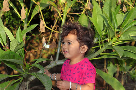 A beautiful Indian child smiles at the garden looking at the white jasmine or Champa flower, india
