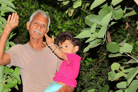 A beautiful Indian child and grandfather smile at the garden looking at the growing beauty of the trees, india
