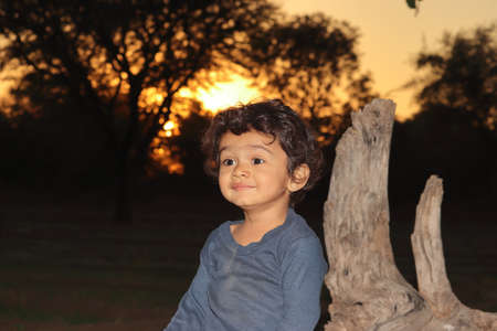 An Indian beautiful smiling little boy child sitting in the field outside at sunset, india. concept for Smiling children, Country's pride today children,childhood, infancy, boyhood,