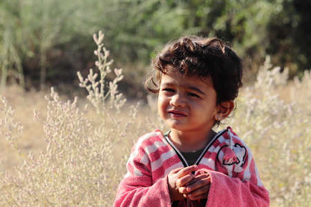 A small boy of Indian origin looking at the camera with small eyes.concept for Today's children tomorrow's future, childhood memories, smile on face, daily routine,Facial Reaction, face expression
