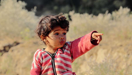 A little boy of Indian origin is seen looking away from his finger and hand. concept for Today's children tomorrow's future, childhood memories, smile on face, daily routine,Facial Reaction, face