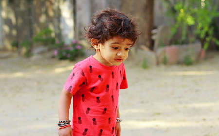 A little boy of Indian origin looking at the ground with astonishment, india.concept for Childhood joys, childhood memories, baby's face expressions and Body language , pretty cute kids