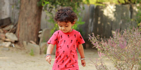 A little boy of Indian origin wearing a red shirt looking down at the ground, india.concept for Childhood joys, childhood memories, baby's face expressions and Body language , pretty cute kids