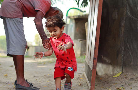 An Indian-origin little boy trying to catch grandpa, india.concept for Childhood joys, childhood memories, baby's face expressions and Body language , pretty cute kids