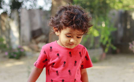 A little boy of Indian origin looking happily towards the ground, india.concept for Childhood joys, childhood memories, baby's face expressions and Body language , pretty cute kids 免版税图像