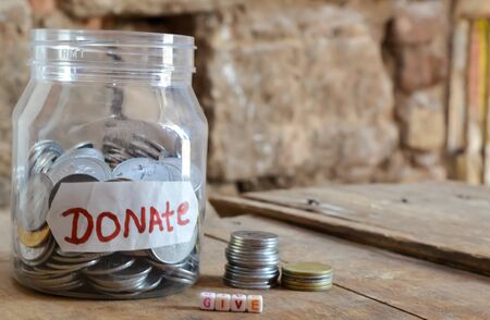 Give donate ,money jar with a label with the word donations on it and wooden ,give donate written text on wooden
