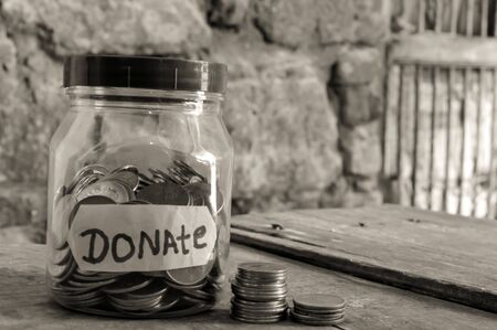 donate written jar and coins ,Money jar full of coins for charity and black photo