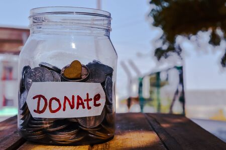 charity or donate written in jar,donate written jar,money jar with a label with the word donations on it and wooden