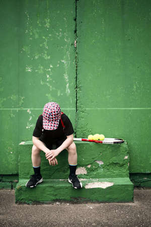 disappointment: Sad tennis player having rest in front of old training wall