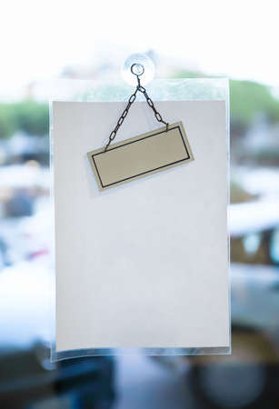 Blank paper sheet for message on glass office door photo