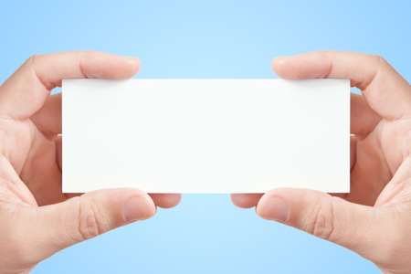 Two man's hands holding long blank paper business card on light blue background, copy space fot your message or adverisment Stock Photo - 8254158