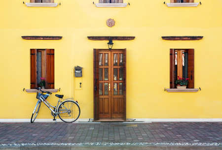 Classic style house entrance (yellow walls, wooden door and windows decorates with flowerpots) and lonely bicycle Stock Photo - 8490143