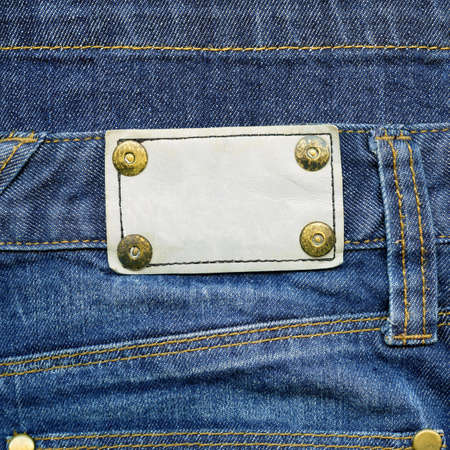Highly detailed closeup of blank grungy leather label with yellow metal rivets on worn blue denim    photo