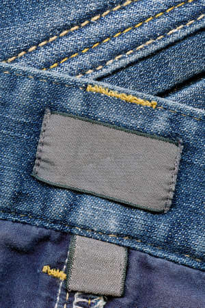 inner wear: Closeup of blank dark cotton labels inside of blue worn jeans, kind of textured background