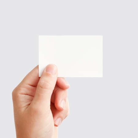 business card in hand: Businessmans hand holding blank white paper business card, closeup isolated on square gray background Stock Photo