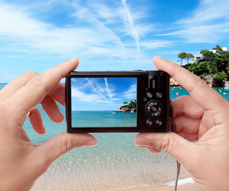 photo camera: Tourists hands holding digital photo camera on vacations, taking picture of beautiful sunny seaside