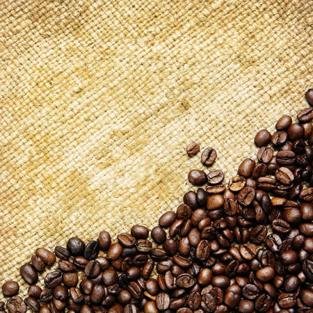 Closeup of fresh roasted coffee beans on traditional rough sack textile background, square photo