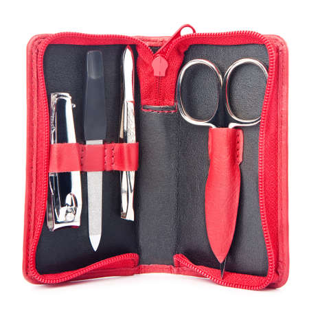 necessary: Small trevelers nail care kit of necessary instruments (scissors, tweezers, neail file and trimmer) in red leather pocket case, isolated on white background Stock Photo