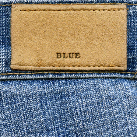 Closeup of word BLUE on blank grungy artificial leather label on worn blue denim, kind of a background photo
