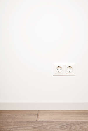 Double electricity power socket (european standard) on blank white wall background over moder wooden floor