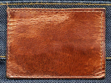 threadbare: Highly detailed closeup of blank grungy brown leather label on vintage dark blue denim, good for background