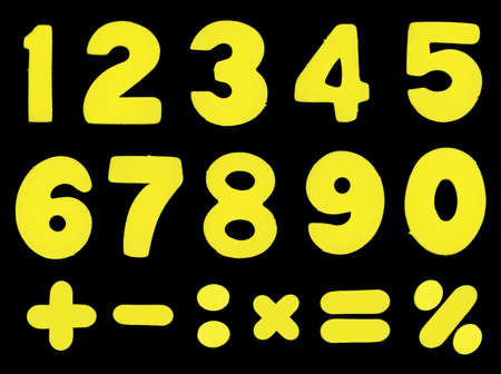simbols: Numbers and mathematic operations simbols made of yellow color sponge-alike soft plastic, isolated on black background