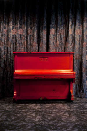 ornated: Vintage red piano in dark theatre or nightclub interior over floral ornated curtains background Stock Photo