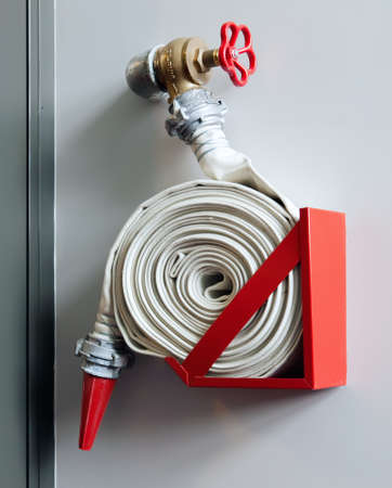 Fire-hose on the wall in a modern building Stock Photo