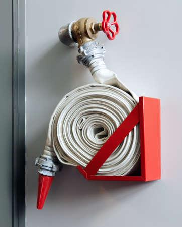 hose: Fuego-manguera en la pared de un edificio moderno