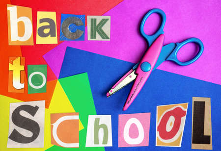 scissors cutting paper: Words Back To School made of handmade magazine clipping ABC on colorful paper with childs scissors