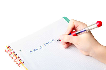 Hand of a child writing words back to school with blue ink pen in a checkered notebook, isolated on white background photo