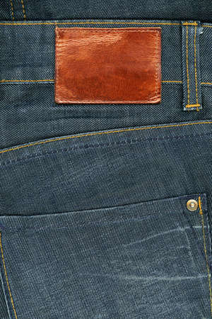 Highly detailed closeup of blank brown natural leather label on dark denim, good for background    photo