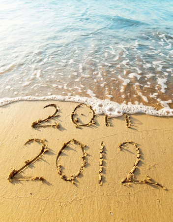 New Year 2012 is coming concept - inscription 2011 and 2012 on a beach sand, the wave is covering digits 2011. photo