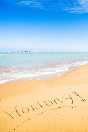 The inscription Holiday! in sunny tropical beach sand photo