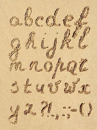 The inscriptipon of handwritten alphabet letters on wet beach sand photo