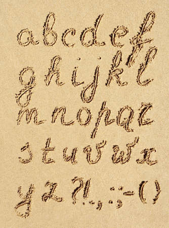 sand drawing: The inscriptipon of handwritten alphabet letters on wet beach sand