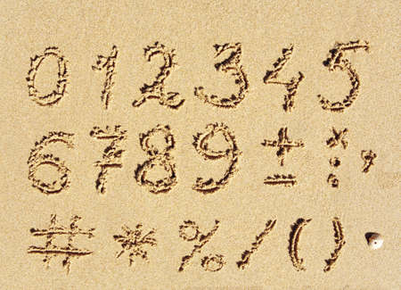 roman alphabet: The inscription of handwritten numbers and math signs on wet beach sand