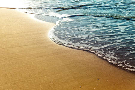 scenic: Shiny tropic sea wave on golden beach sand in sunset light Stock Photo