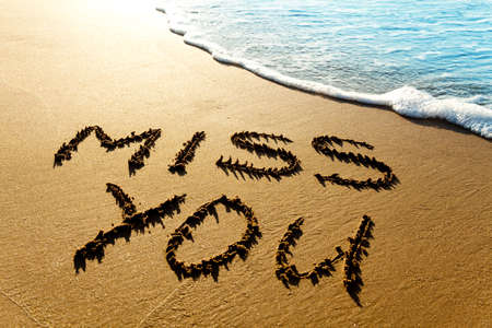 conceptional: Dramatic inscription Miss You on wet golden beach sand in sunset light