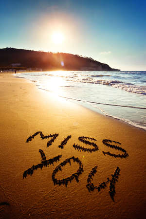 Dramatic inscription Miss You on wet golden beach sand in sunset light photo