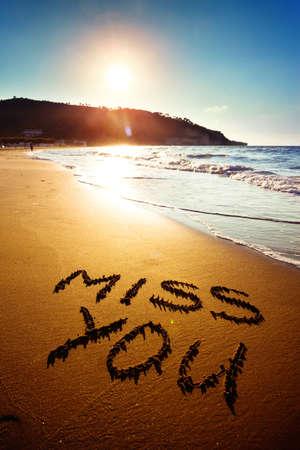 Dramatic inscription Miss You on wet golden beach sand in sunset light