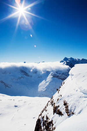Sun and clouds over winter mountains, covered with snow  photo