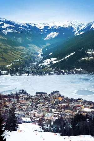 Aeral view down on Zell Am See (Austria, Alpes) town, frozen lake, ski resort and mountains in fog. photo